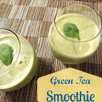 green tea smoothies in stemless wine glasses topped with a spinach leaf