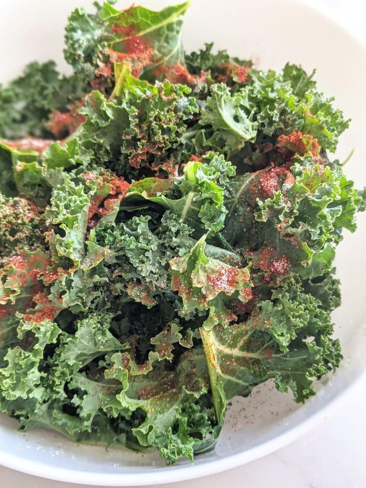 kale leaves in a bowl with seasonings