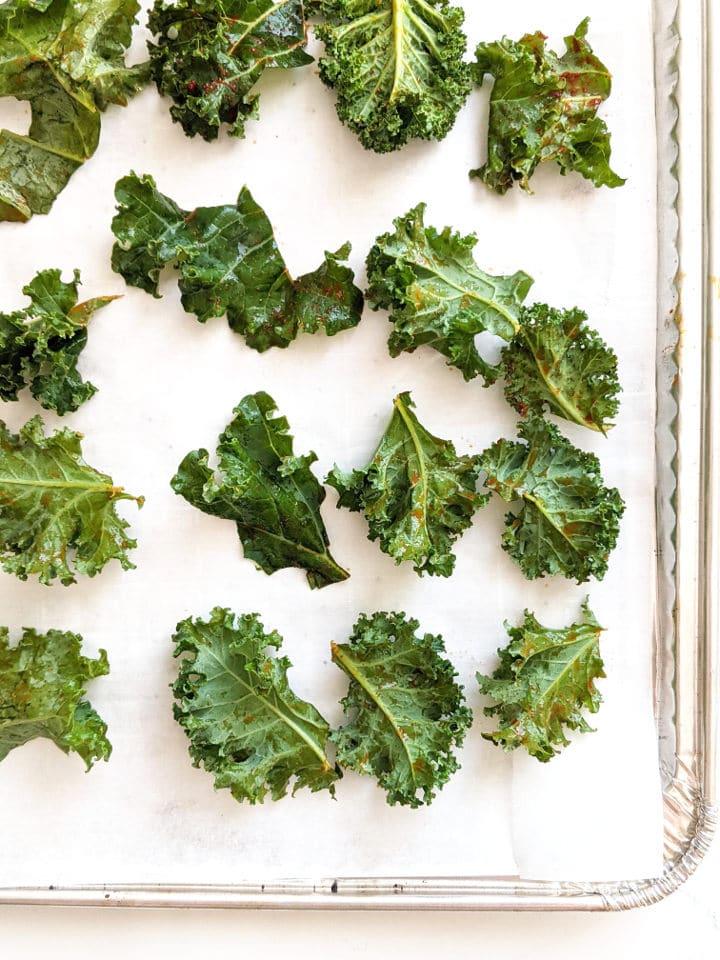 seasoned kale leaves on a baking sheet