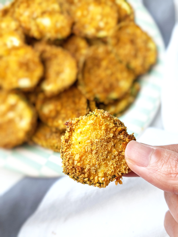 These Vegan Baked Zucchini chips are oven-baked, crispy, and irresistible! They're a delicious and healthy alternative to regular chips and are incredibly easy to make! #vegansnack #veganchips #healthysnack #easysnack #bakedchips #zucchinichips