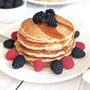 A stack of pancakes on a plate with fresh berries and a drizzle of maple syrup