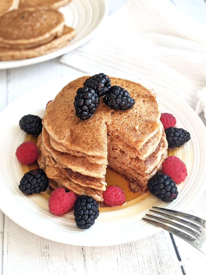 A stack of pancakes on a plate with fresh berries and maple syrup with a slice taken out of the stack.