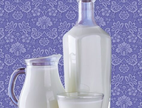 A glass, a jug, and a large bottle all full of milk
