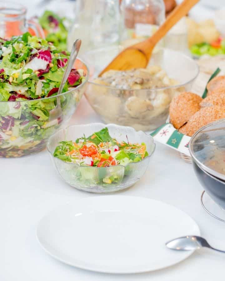 potluck style table set with salad and other dishes