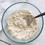 Quick and easy vegan ricotta made with cashews! No oil or soy. It's sweet and tangy--the perfect replacement for dairy ricotta. Healthy, easy, and delicious! Use as a dip, in lasagna, stuffed shells, spread on toast or crackers or add on top of salads! #vegancheese #cashewricotta #dairyfree #cashewcheese #plantbasedcheese