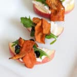 Apple slices covered with vegan cream cheese, a drizzle of balsamic glaze, an arugula leaf, and wrapped in carrot bacon