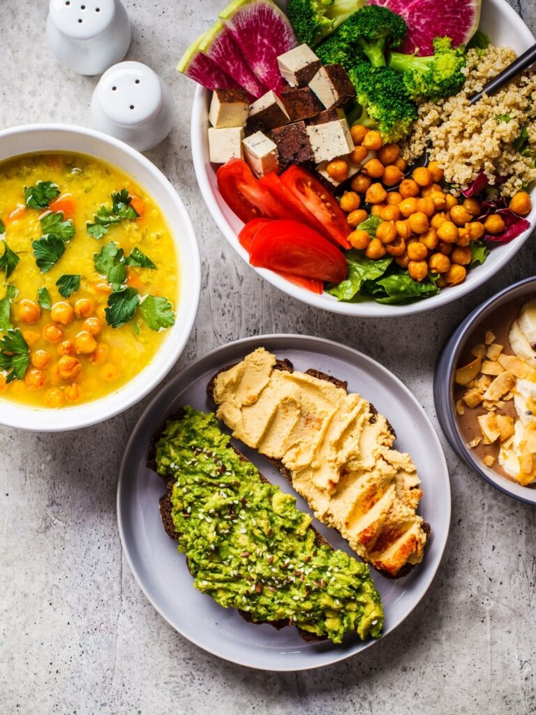 Several bowls of colorful vegan food including soup, toast with different spreads, vegetable and bean bowl, and chocolate nice cream with nuts on top.