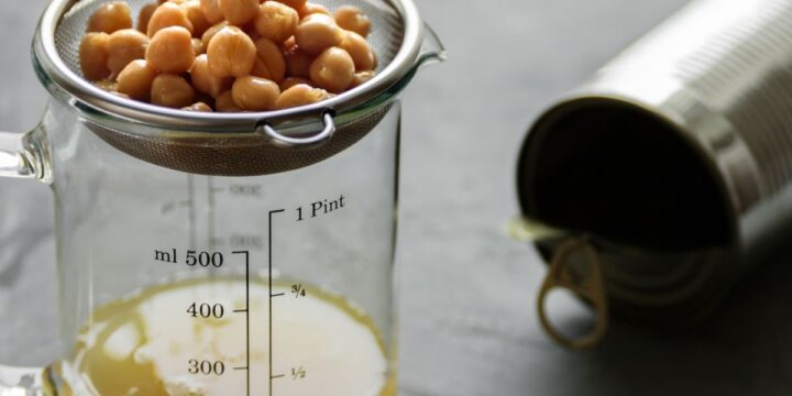 chickpeas strained over a measuring cup to capture the liquid aka aquafaba