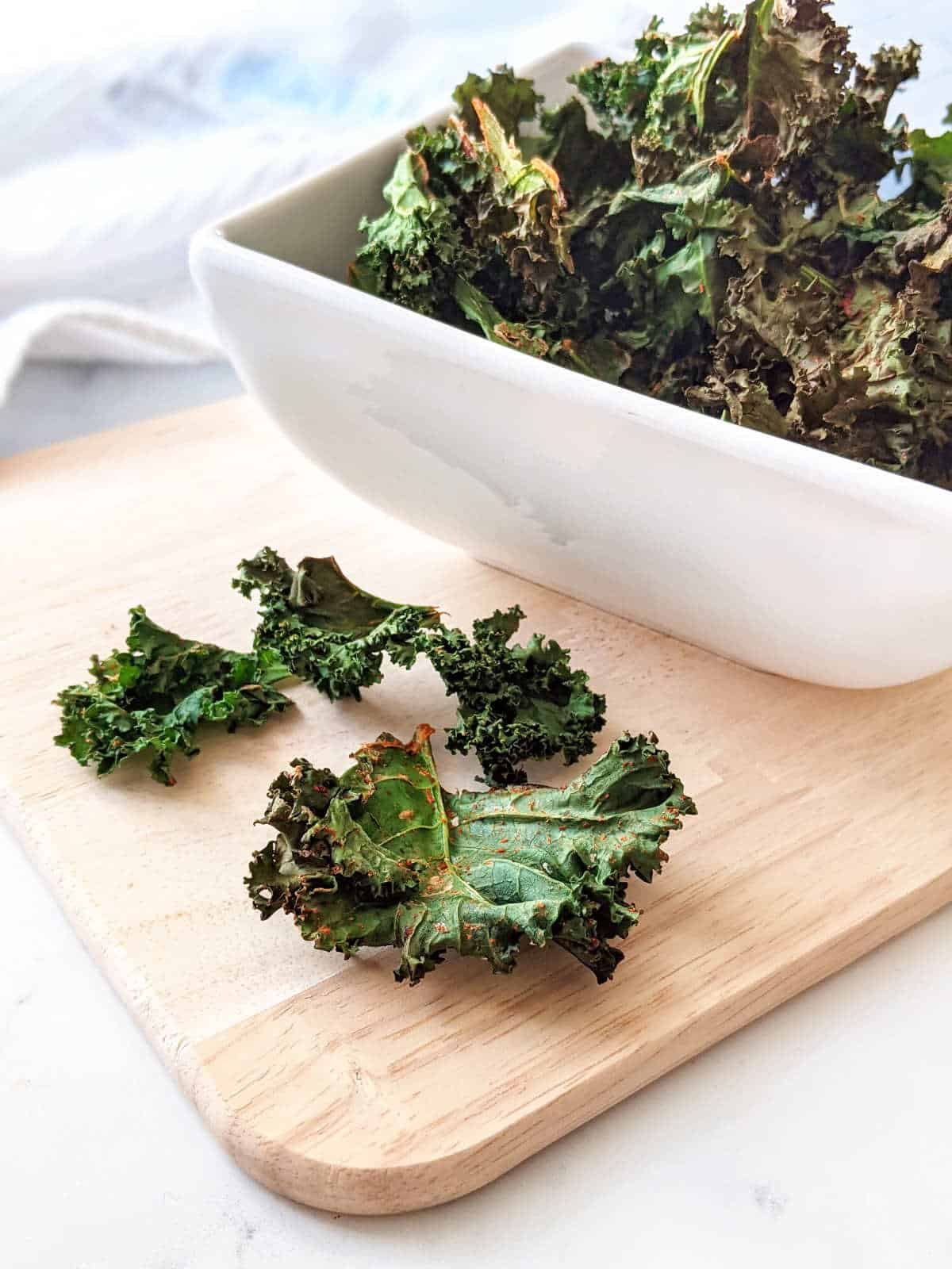 A bowl of kale chips on a cutting board with some chips on the cutting board next to the bowl.