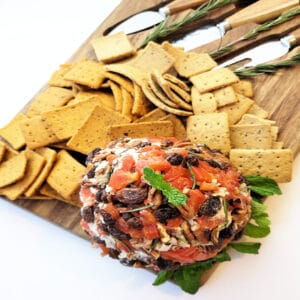 vegan cheese ball on board arranged with crackers