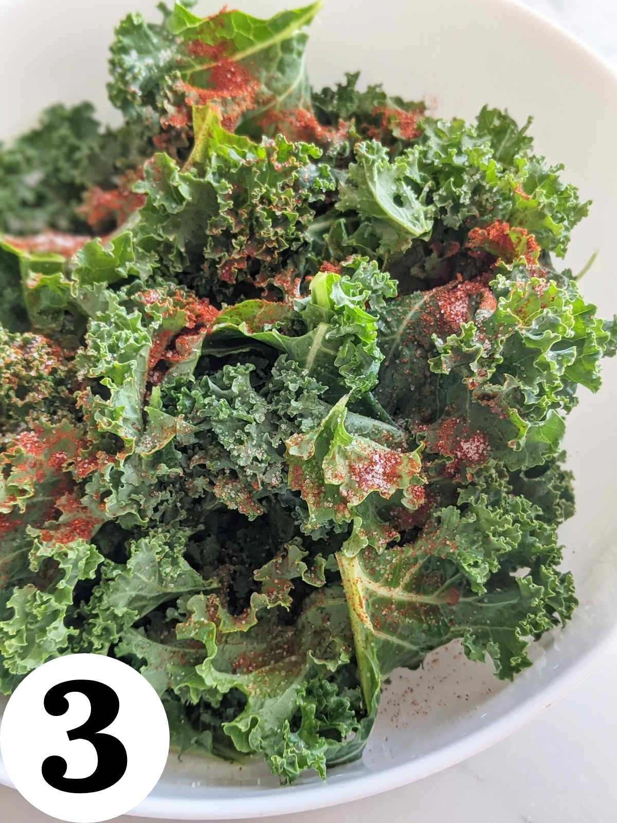 Chopped kale leaves in a bowl with seasonings.