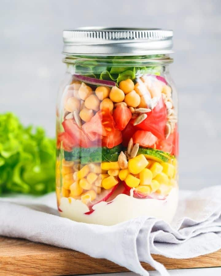 Meal prepped mason jar full of colorful salad ingredients like tomatoes, chickpeas, and corn, with a creamy dressing one the bottom.