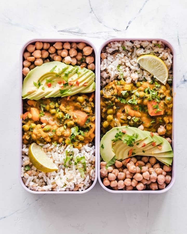 Two bento boxes side by side full of chickpeas, rice, and avocado.