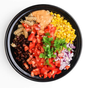 A bowl of unmixed taco salad ingredients
