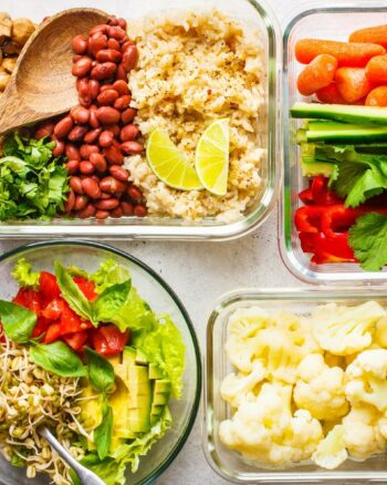 Several meal prep containers full of colorful food