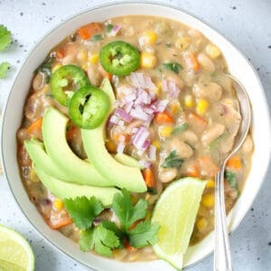 white bean chili in a bowl topped with avocado, cilantro, jalapeno slices, and lime