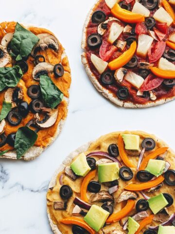 three healthy pita pizzas with lots of veggies and toppings