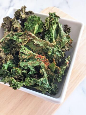 Kale chips in a bowl on a cutting board