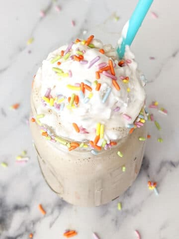 Birthday cake shake topped with coconut whipped cream and sprinkles
