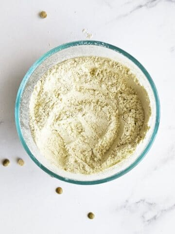 homemade protein powder in a bowl with split peas around it