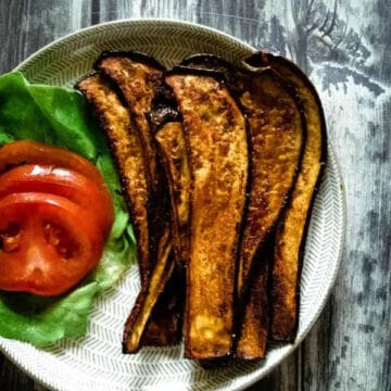 eggplant bacon on a plate with tomatoes and lettuce