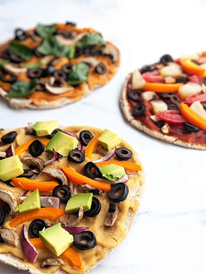 up close image of three pita pizzas with a variety of toppings and sauces
