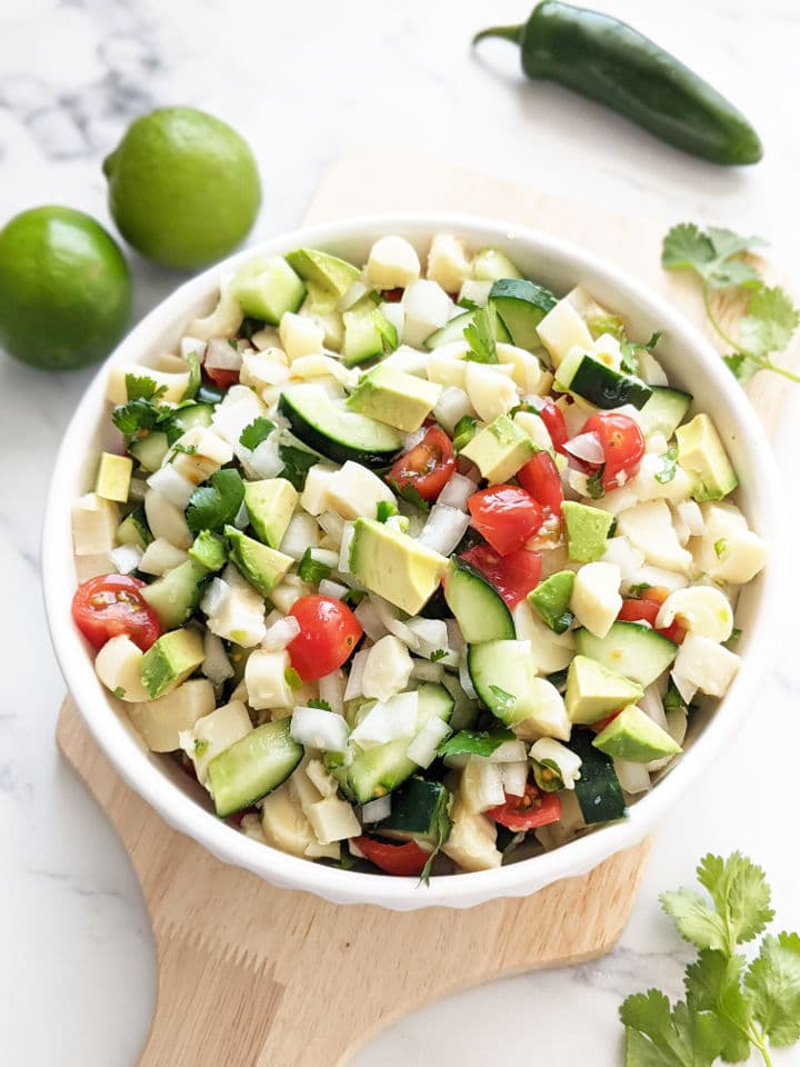 Palmito ceviche in a bowl on top of a cutting board with limes, cilantro and a jalapeno pepper