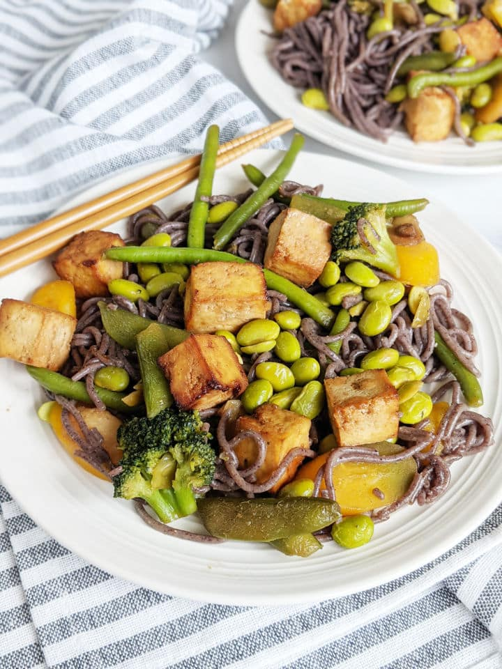 Tofu and vegetable stir fry with black rice noodles on a plate with chopsticks