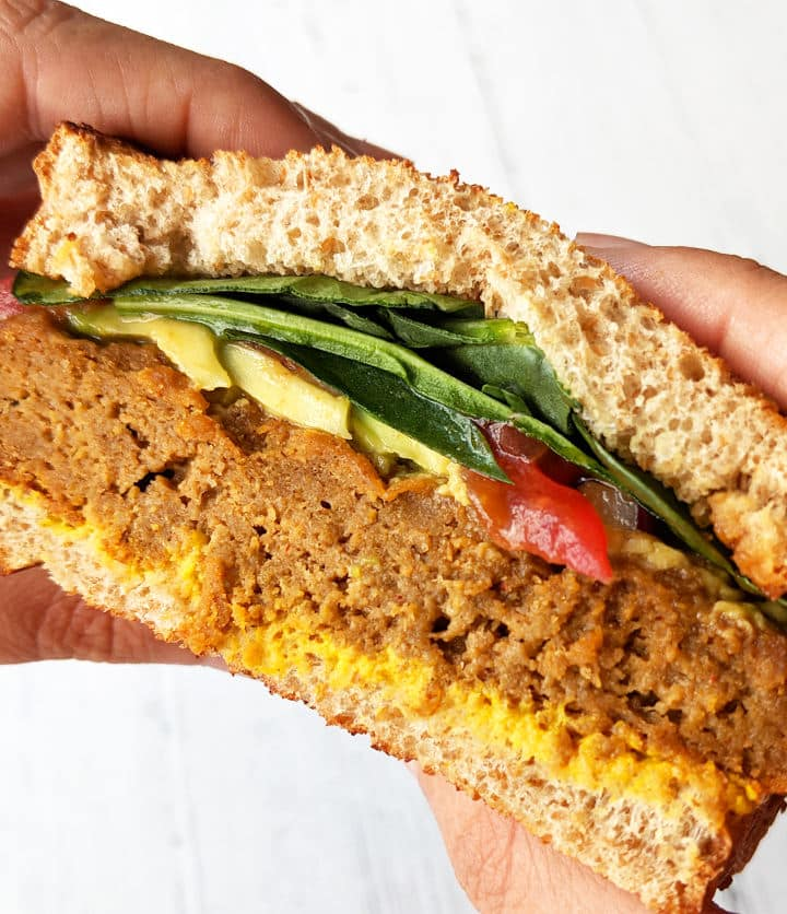 Up close shot of hands holding a BBQ Seitan Sandwich topped with veggies, avocado, and mustard