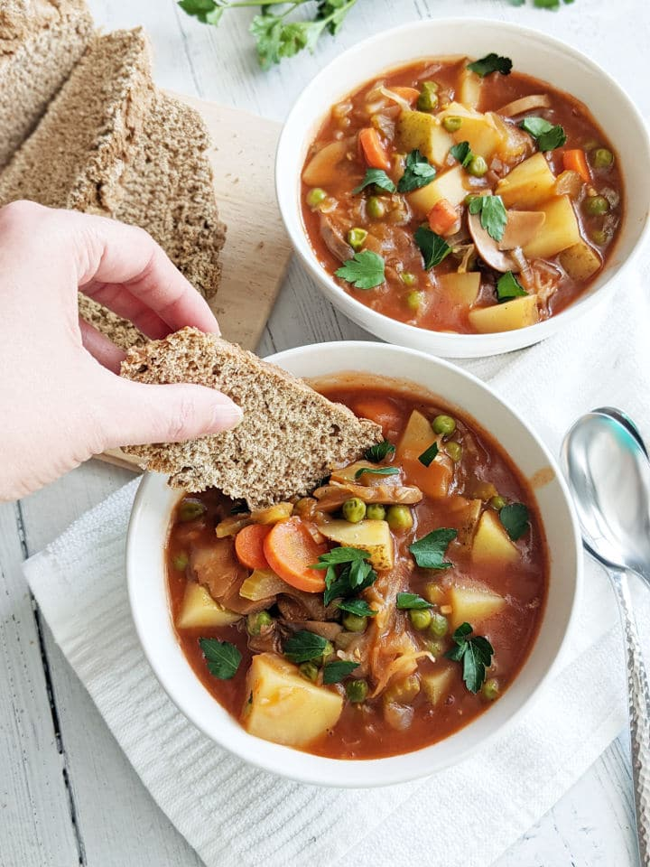 A bowl of vegetable stew topped with parsley with a hand dipping a slice of soda bread into the stew