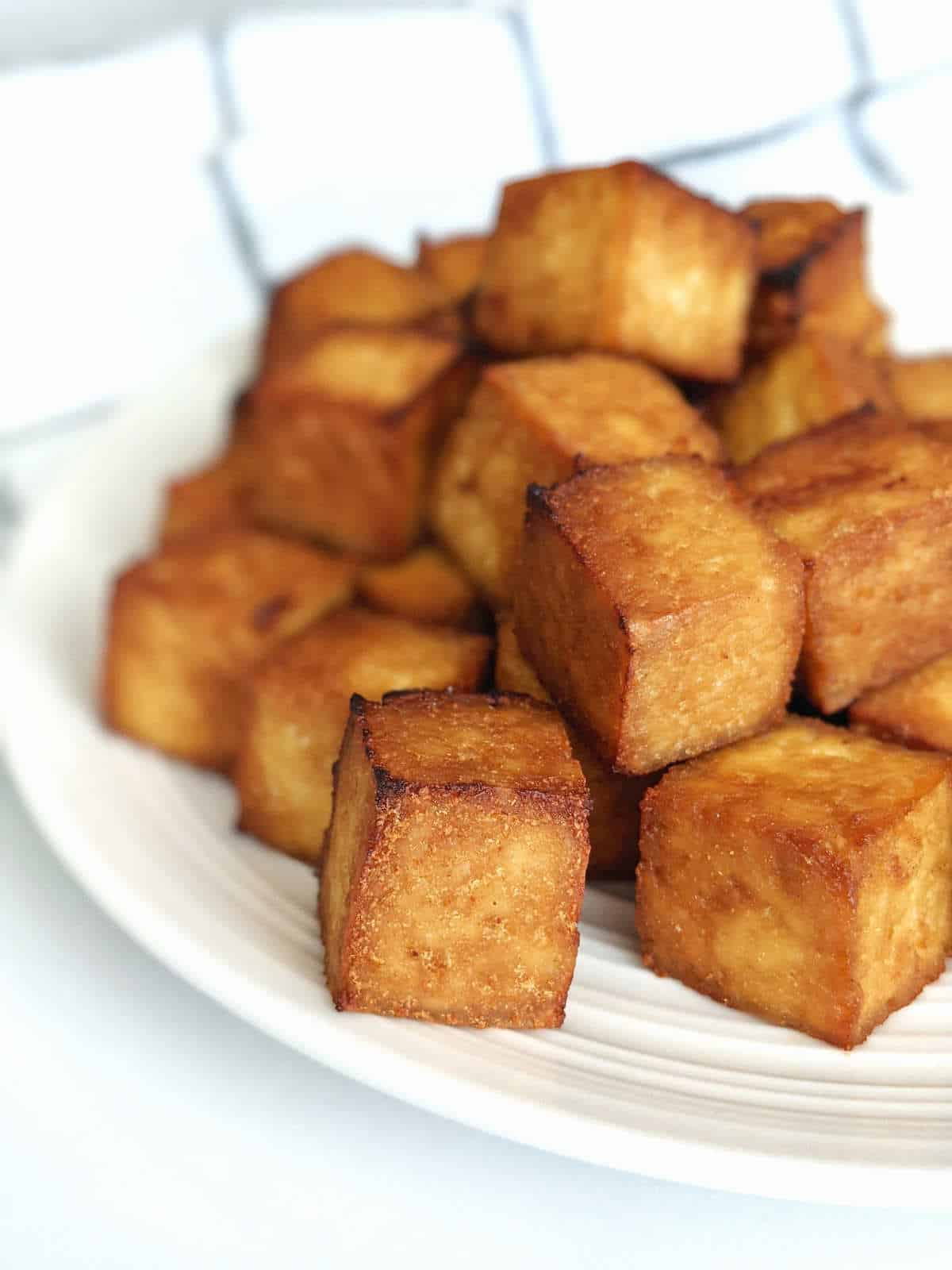 Crispy cubed tofu stacked on a plate.