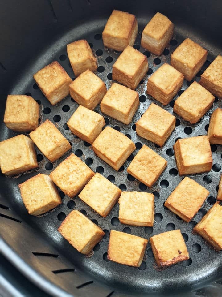Tofu cubes in an air fryer basket