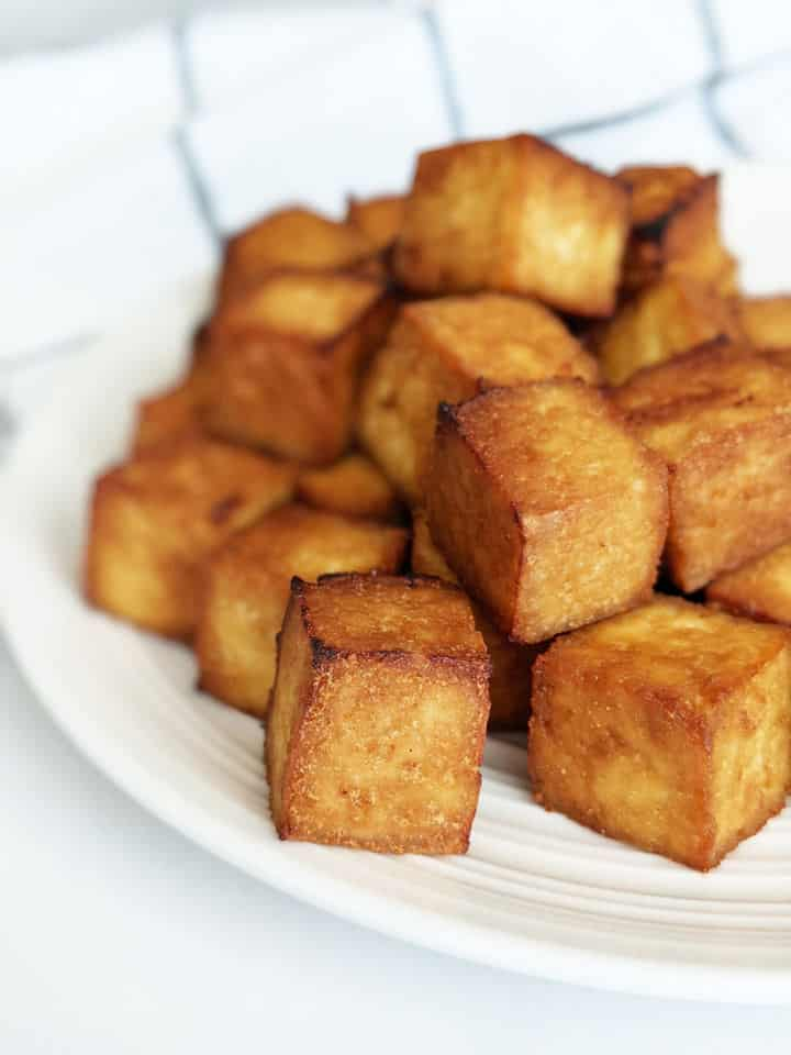 Crispy cubed tofu stacked on a plate