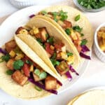 Vegan tofu tacos on a plate with ingredients in small bowls surrounding it