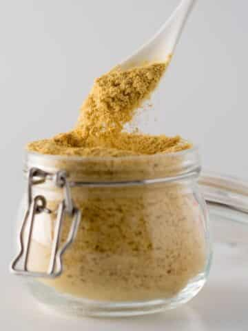 Spoon scooping nutritional yeast out of a glass jar