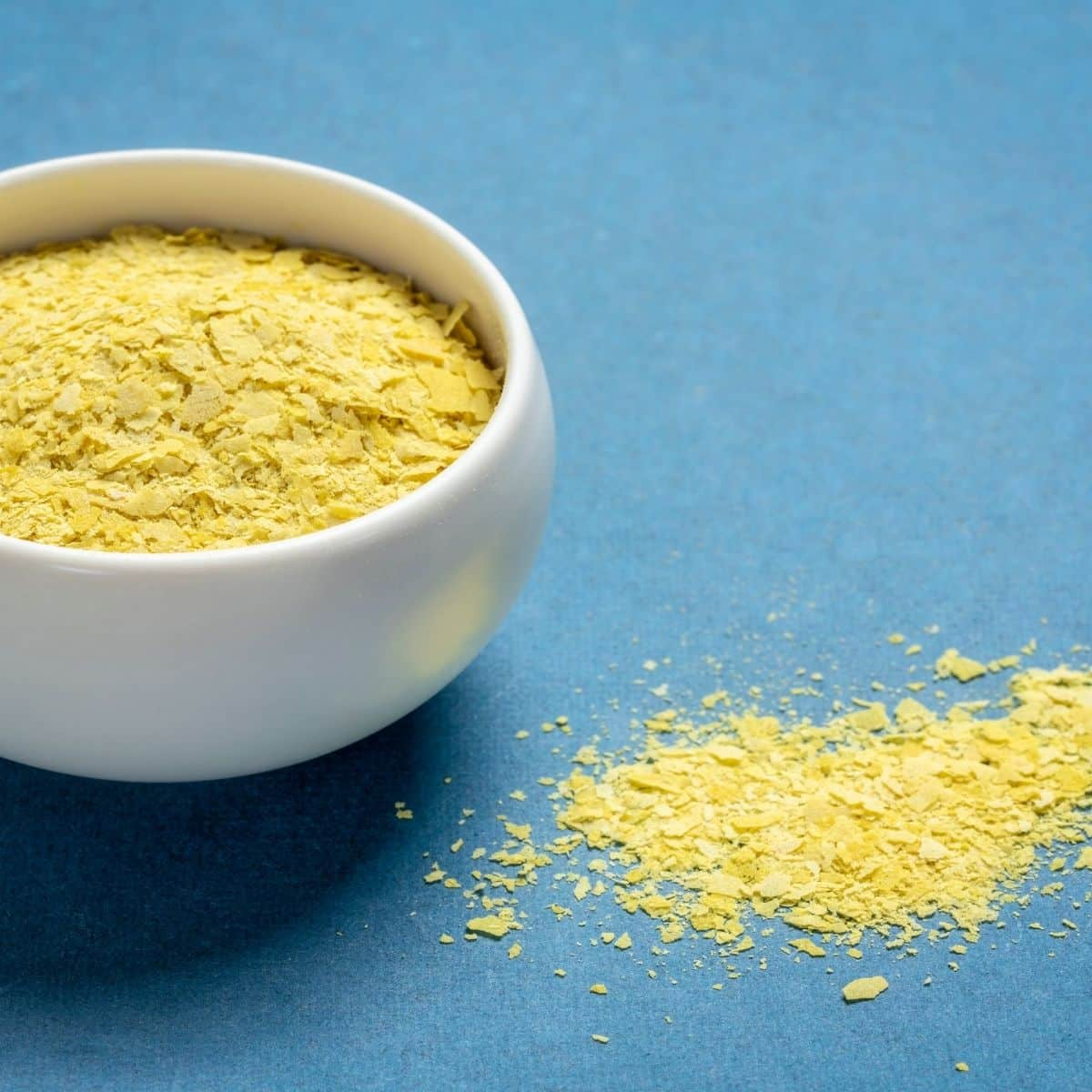Nutritional yeast in a bowl with some spilt next to it