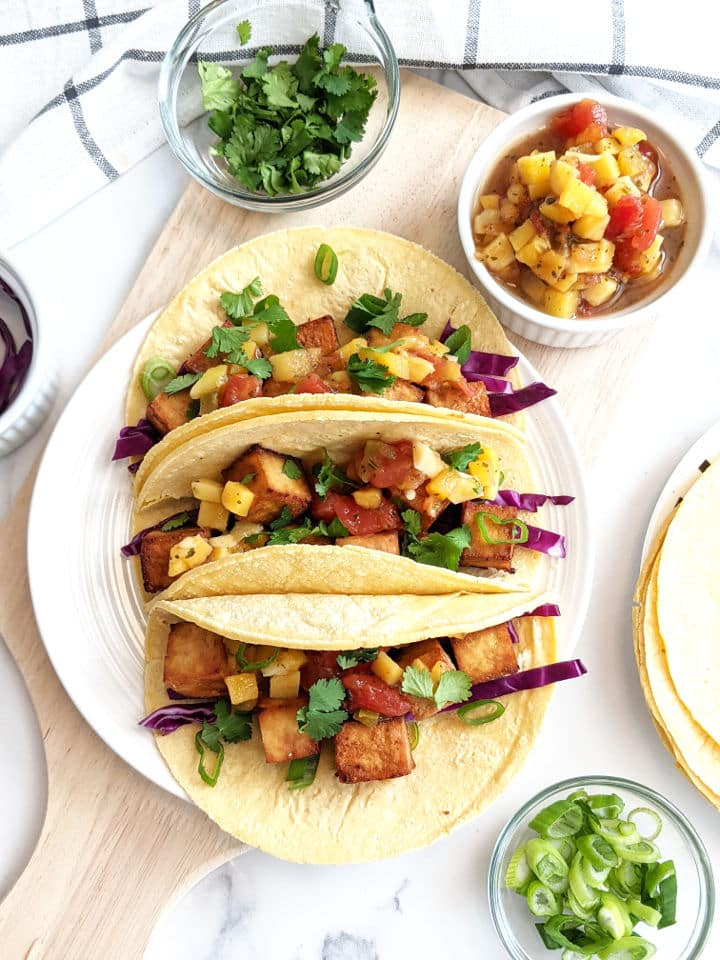 Over head shot of finished tofu tacos on a plate surrounded by additional toppings