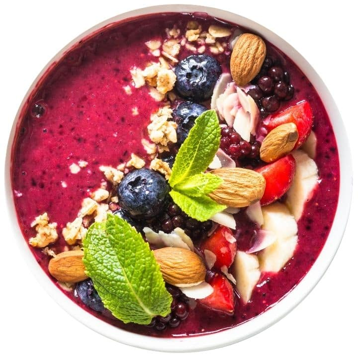 Smoothie bowl topped with berries, nuts and fresh basil