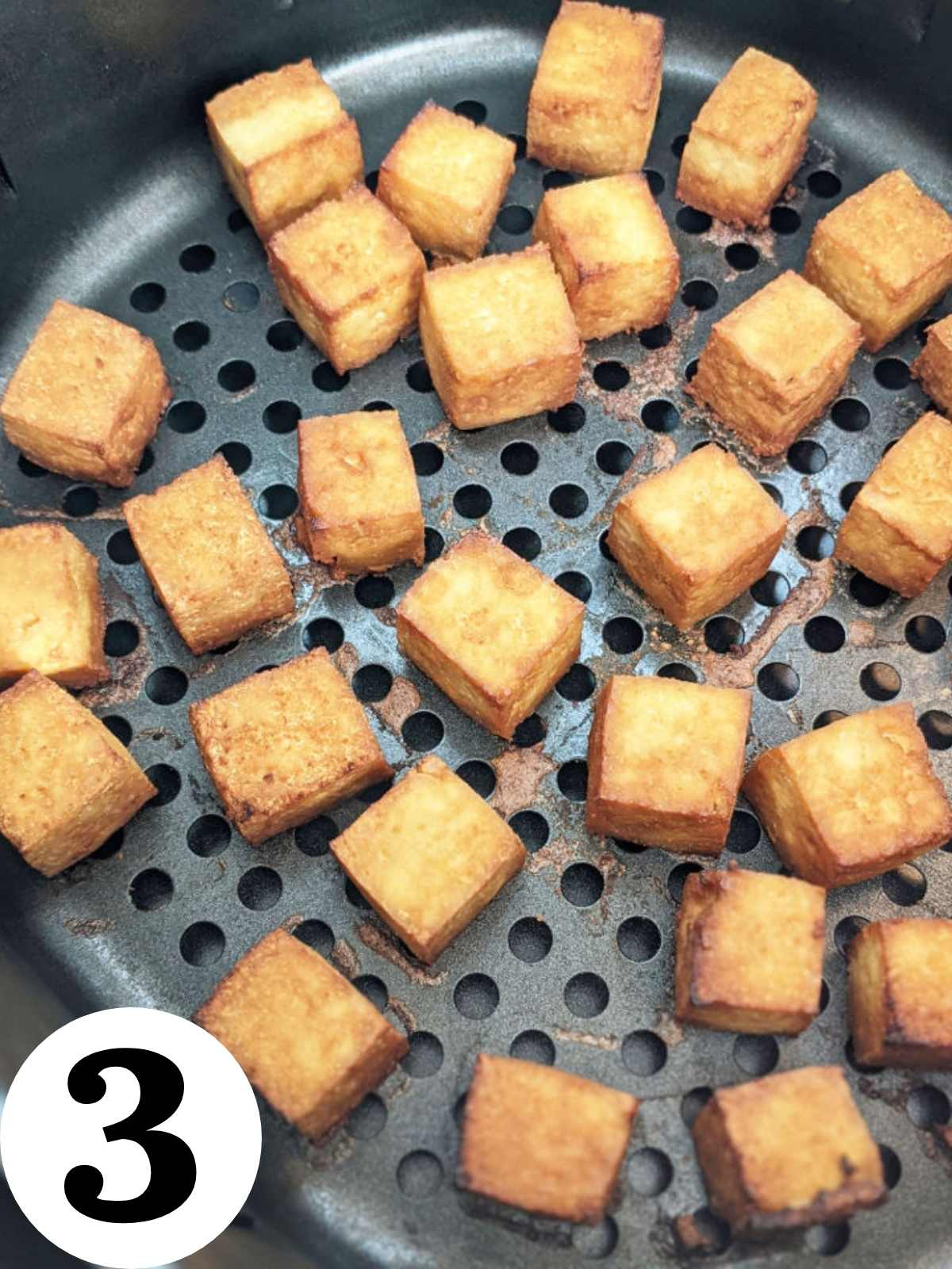 Tofu cooking in an air fryer.