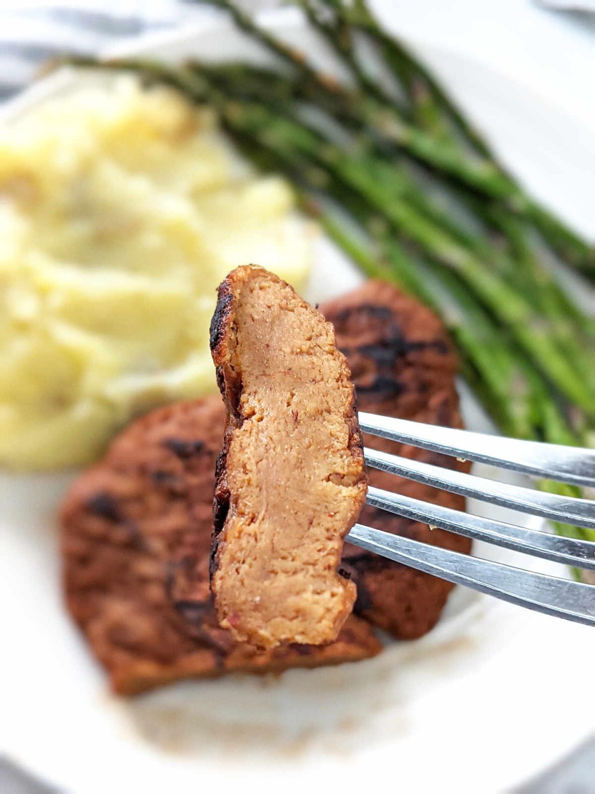 Up close of fork holding a slice of vegan steak