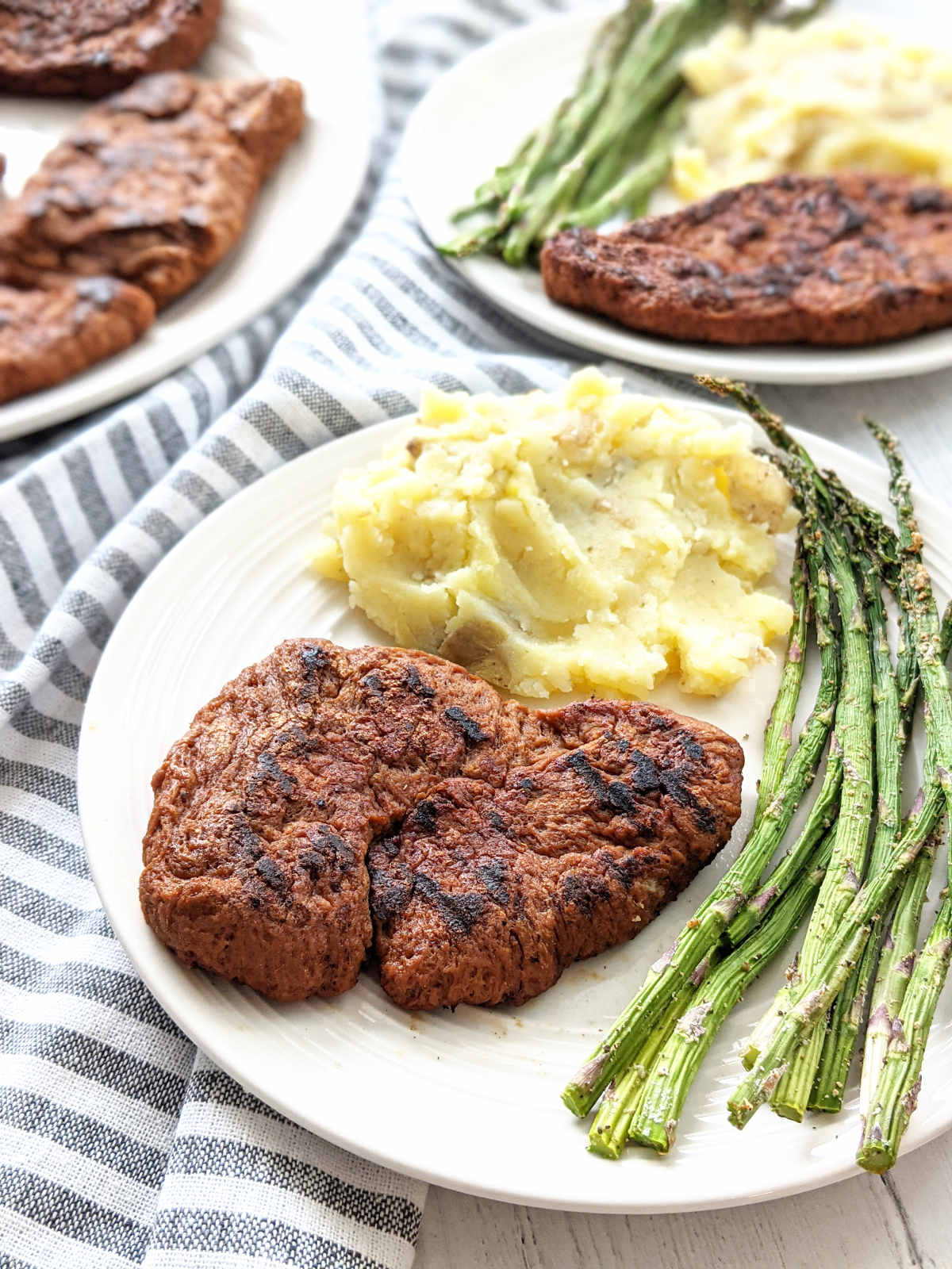 Vegan steak on a plate with mashed potatoes and roasted asparagus