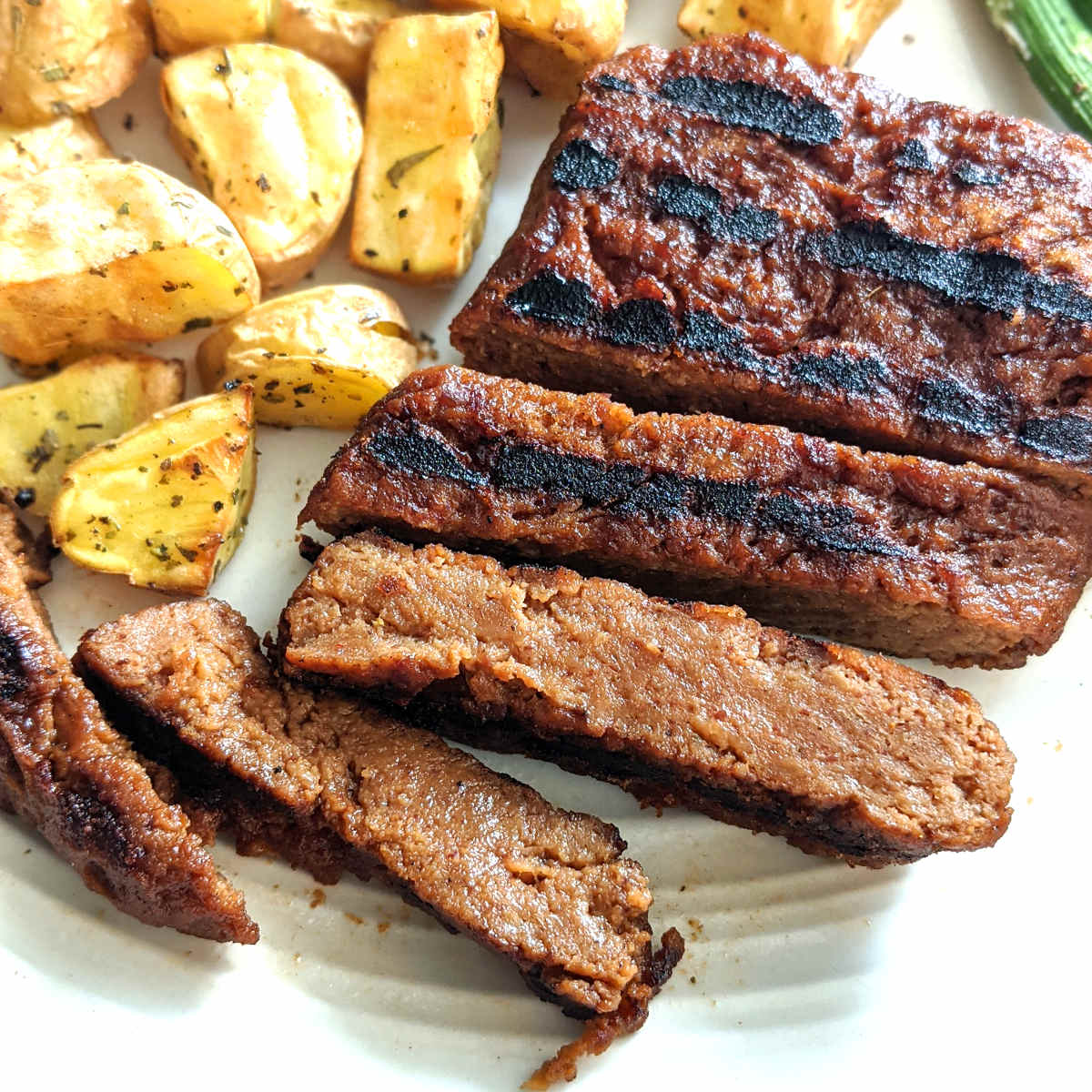 Vegan steak cut into slices on a plate with golden potatoes.