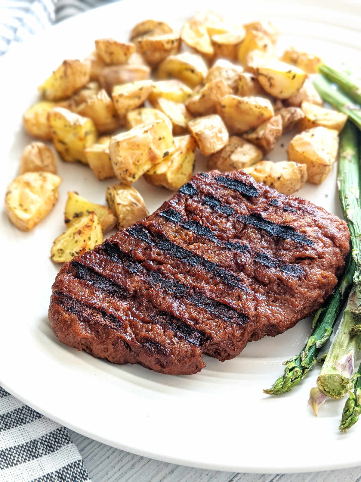 A vegan steak on a plate with potatoes and asparagus.