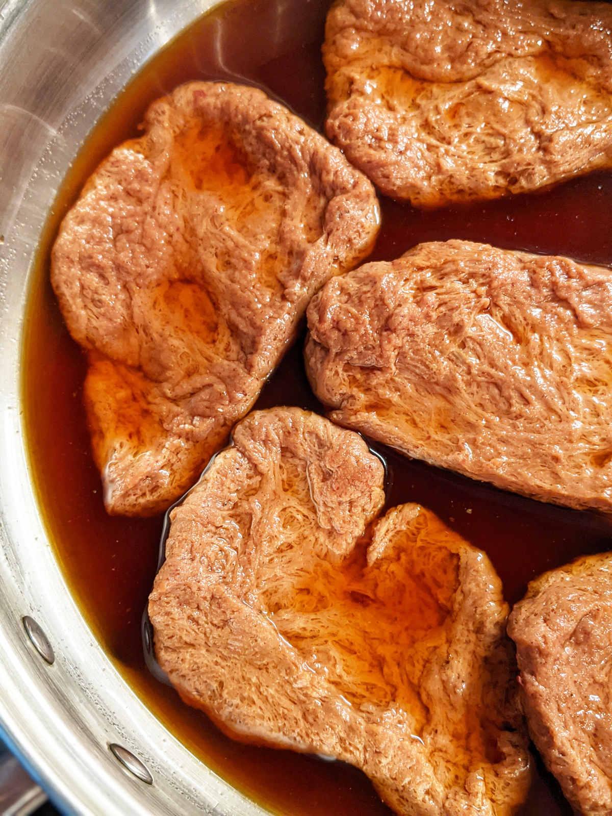 Vegan steaks in broth in a skillet