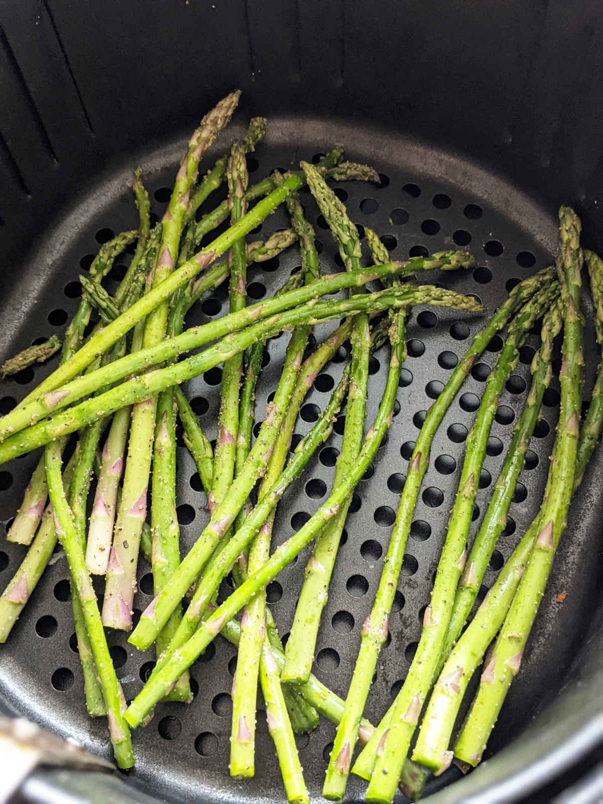 Up close of asparagus seasoned and ready to be cooked in an air fryer basket