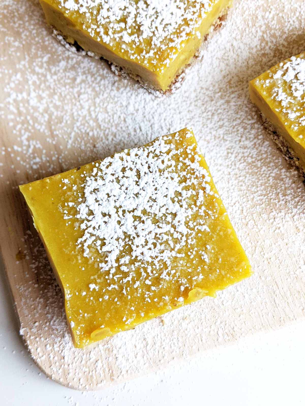 Cut lemon bars on a cutting board topped with powdered sugar