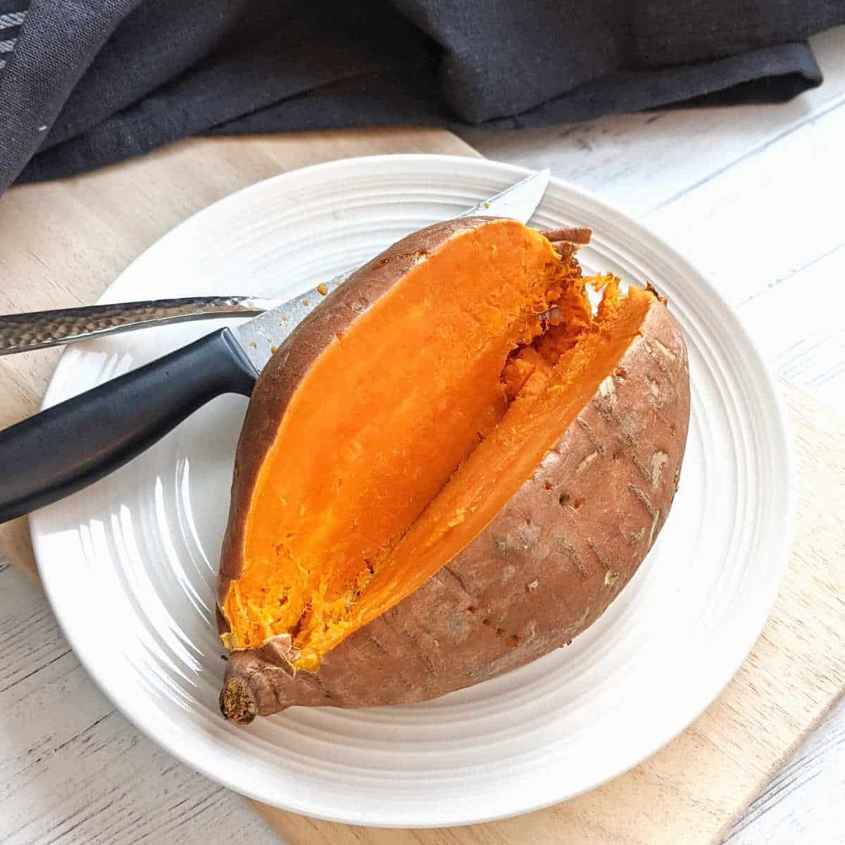 A sliced open cooked sweet potato on a plate with a fork and knife.