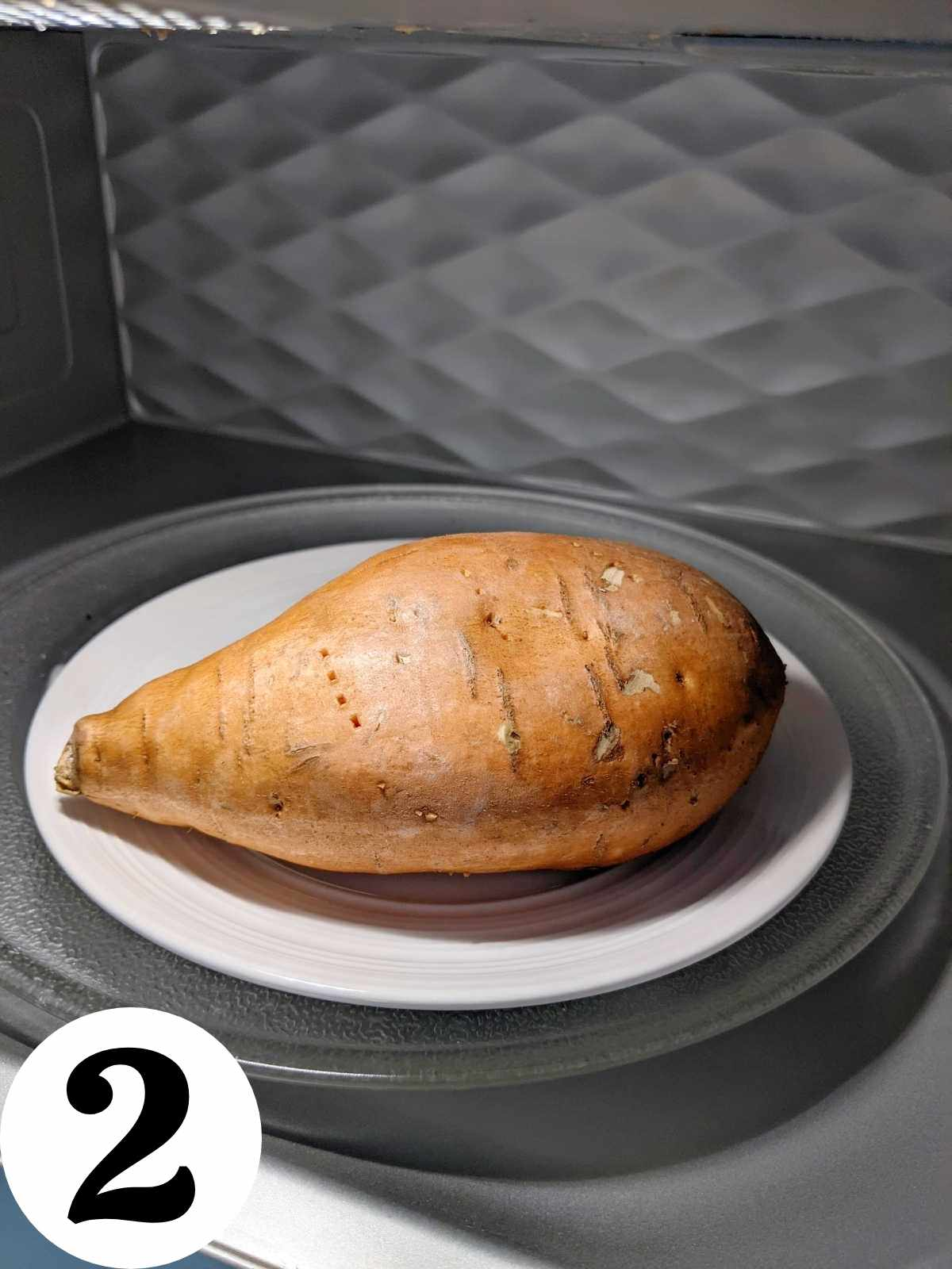 A prepared sweet potato on a plate in the microwave.