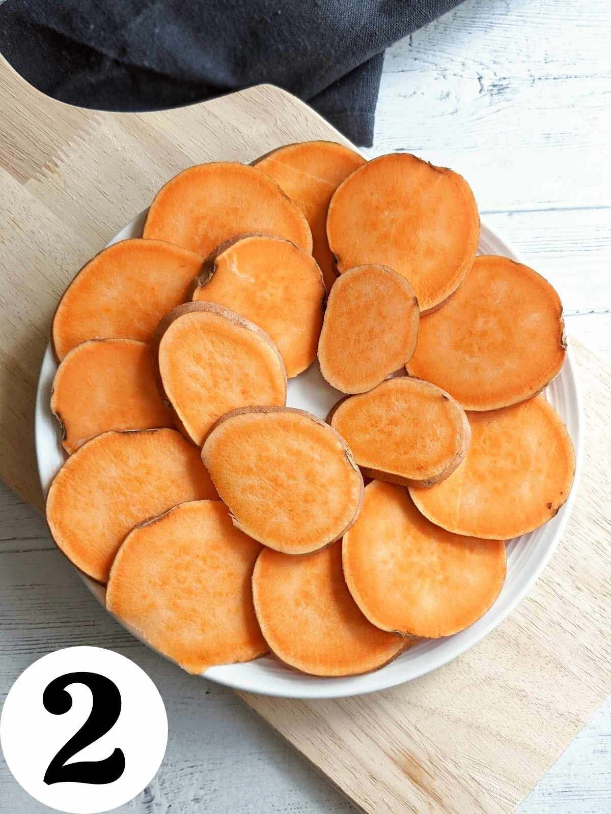Sliced sweet potato arranged on a microwave-safe plate.
